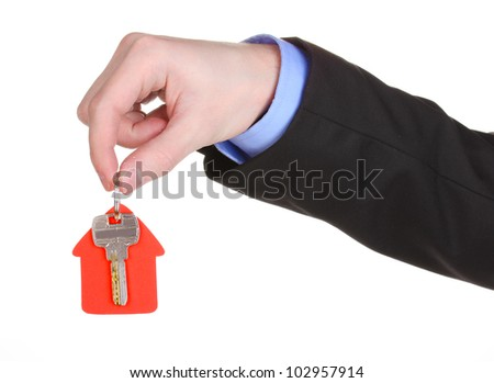 Key with house-shaped charm in hand isolated on white - stock photo