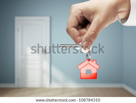 key with key chain in hand against backdrop of rooms - stock photo