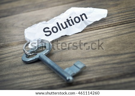Key with message Solution on wooden table