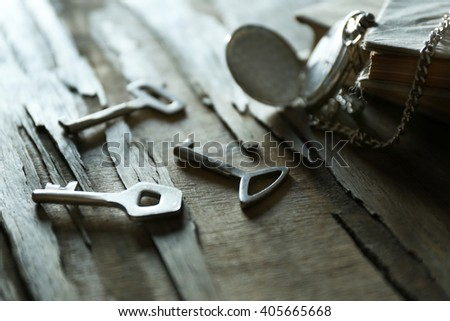 Key with pocket watch and books on rustic wooden background