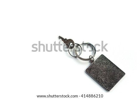 Key with rectangle key chain on white background. - stock photo