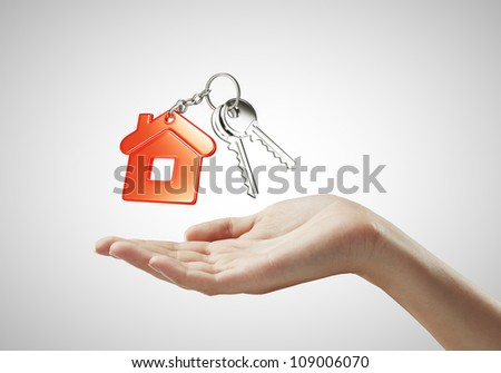 key with  red key chain in hand on white background - stock photo