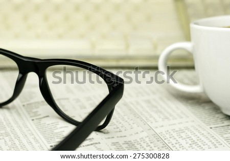 keyboard ,a cup of coffee and a black eyeglasses on a financial newspaper with a very shallow depth of field with copy space for text