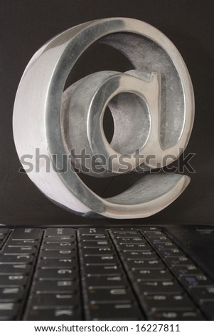Keyboard and arroba in black background - stock photo