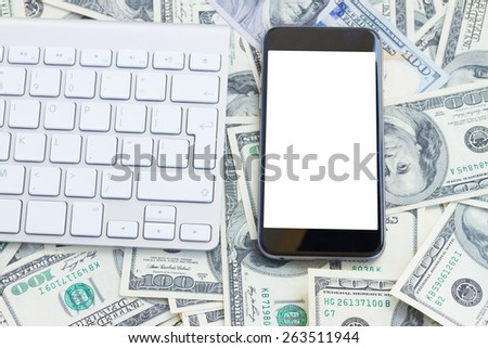 keyboard and modern phone  on money background - stock photo