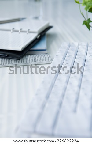 Keyboard and notebook placed on a desk