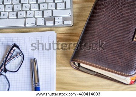 Keyboard and office supplies on the wooden table