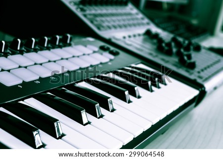 keyboard, piano, synthesizer & digital mixer in home studio for music background - stock photo