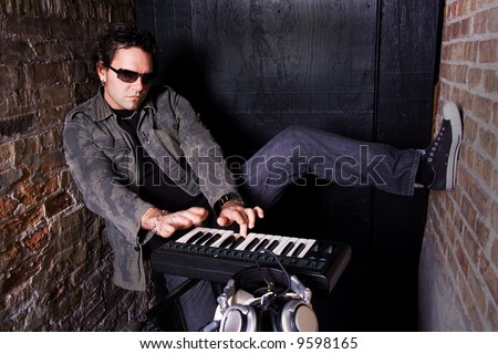 Keyboard player grooving on synthesizer in basement - stock photo
