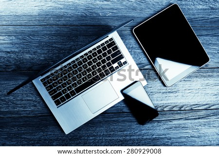 keyboard with phone and tablet pc on wooden desk.  Blue toned - stock photo