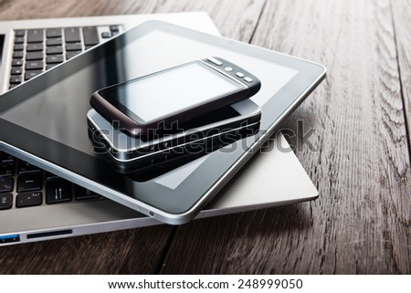 keyboard with two phones and tablet pc on wooden desk  - stock photo