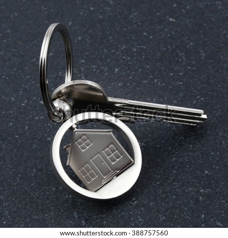 Keychain figure of house and key on stone table - stock photo