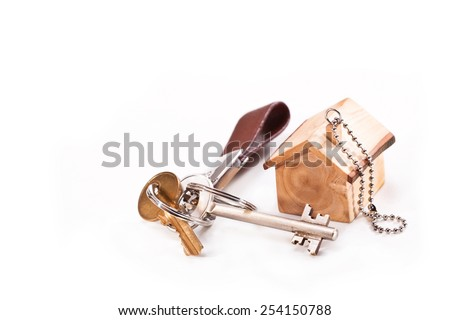 Keychain in the shape of the house is made of olive wood and keys on a white background - stock photo