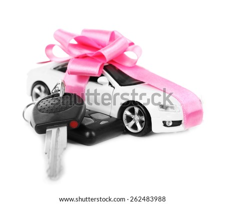 Keys and car with pink bow as present isolated on white - stock photo