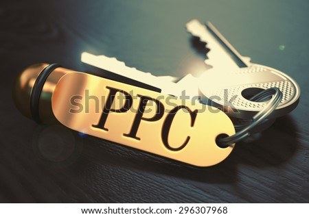 Keys and Golden Keyring with the Word PPC - Pay Per Click - over Black Wooden Table with Blur Effect. Toned Image. - stock photo