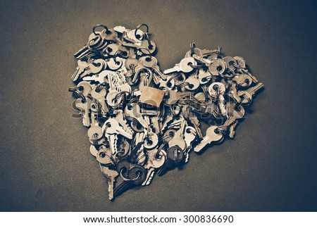 keys arranged as a heart shape with a security lock - stock photo