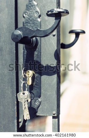 Keys hanging from lock on door with door knob - stock photo