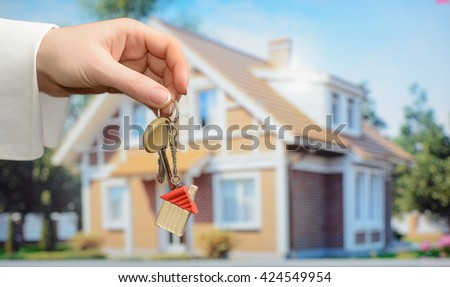 Keys in hands on house background - stock photo