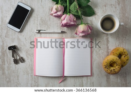 Keys, mobile phone, bouquet of roses, open notebook and food on white wooden table, top view