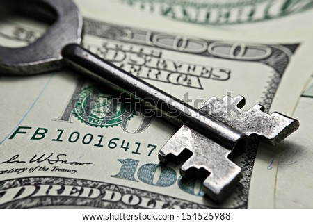 Keys on a one hundred dollar banknote. Pincushion lens use. - stock photo