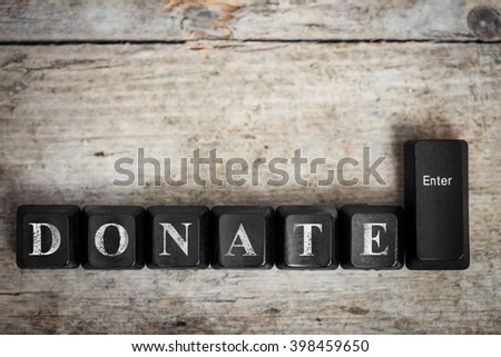 keys on a wooden table with the word donate, conceptual - stock photo