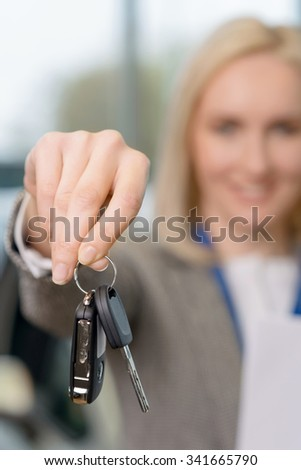 Keys to the vehicle. Close up of car keys upheld by female sales representative.