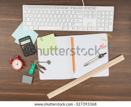 Keys with office supplies on wooden table - stock photo