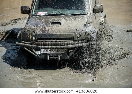 KHABAROVSK, RUSSIA - April 30, 2016: The Suzuki Jimny drive fast through dirty puddles