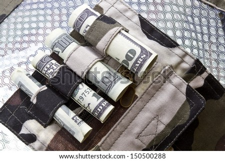 Khaki uniform with dollar rolls. Main weapon is money  concept shot. - stock photo