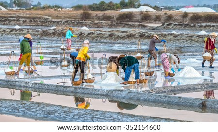 Khanh Hoa, Vietnam, June 30th, 2015: Farmers pour salt in fields with bent shoulders pour salt into collecting basket carry ashore, all hardships that make beauty of labor farmers Khanh Hoa, Vietnam - stock photo