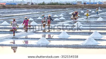 Khanh Hoa, Vietnam, June 30th, 2015: Farmers salt burden going down levees on shoulders with burden full salt align hurried step embankments salts around waiting for them burdens in Khanh Hoa, Vietnam - stock photo
