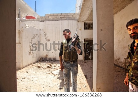 KHANSHEIKHOUN, SYRIA - JUNE 20, 2012: Unidentified Free Syrian Army soldiers  visit shelled area following air strike by Assad government on June 20 2012, in Kahnsheikhoun, Syria - stock photo