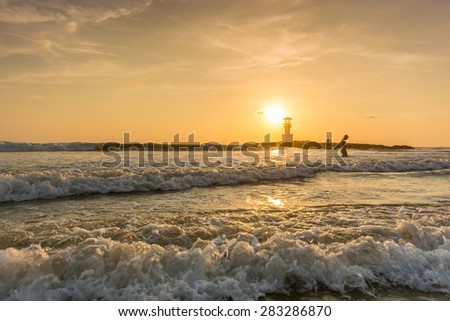 Khao Lak ,Thailand - April 17,2015 : tourist on the beach and sea near Khao Lak lighthouse on sunset in Khao Lak ,Thailand.