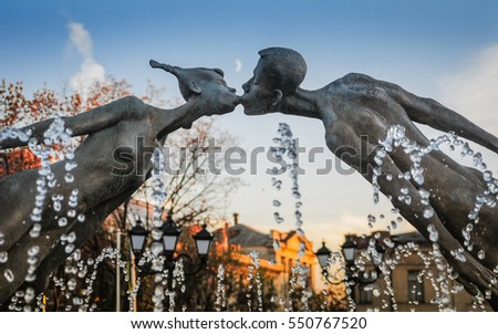 Kharkiv, Ukraine. April 26, 2009. The monument of love on the background of the fountain jets and evening sky with a moon visible at sunset. Two figures kissing.
