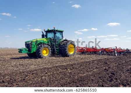Kharkiv, Ukraine - April 13, 2017: Tractor with trailed planter working in field in a sunny spring day in Kharkiv Oblast, Ukraine on April 13, 2017