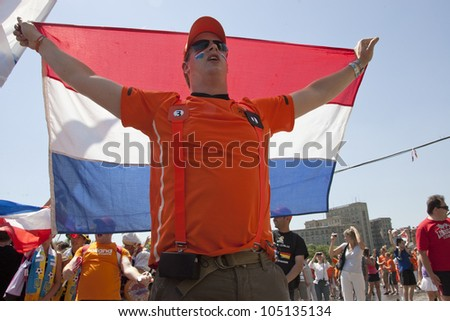 KHARKIV, UKRAINE  JUNE 13: Dutch fan holding a national flag before a UEFA Euro 2012 football match between Germany and Netherlands on June 13, 2012 in Kharkiv, Ukraine - stock photo