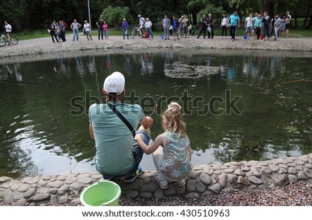 Kharkiv, Ukraine - June 1, 2015: Father and daughter try to catch trout in Sarzhyn Yar city park.