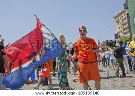 KHARKIV, UKRAINE  JUNE 13: Happy Dutch fan holding a national flag before a UEFA Euro 2012 football match between Germany and Netherlands on June 13, 2012 in Kharkiv, Ukraine - stock photo