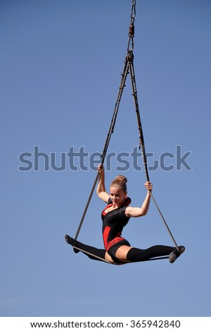 Kharkov, Ukraine - September 27, 2015: Feldman Ecopark in Kharkov on September 27, 2015. Show of trapeze artists. Young woman gymnast. On sky background. Trapeze artist in the sky.