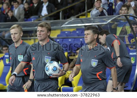KHARKOV, UKRAINE - SEPTEMBER 23: Referee and lines men enter the pitch during FC Metallist (Kharkov) vs. FC Shakhtar (Donetsk) soccer match, September 23, 2009 in Kharkov, Ukraine.