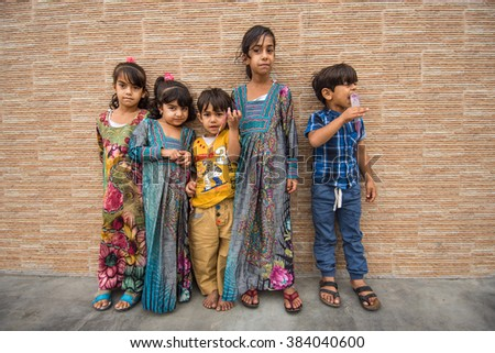 KHASAB (MUSANDAM), OMAN - DECEMBER 27: Small unidentified children in Khasab street on December 27, 2015. On Musandam peninsula lives combination  of Omani, Iranians and other nations of Persian Gulf.