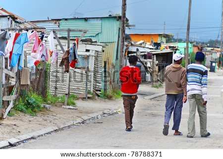 KHAYELITSHA, CAPE TOWN - MAY 22 : A unidentified group of men walk on the street in Khayelitsha township, the name is Xhosa for New Home, on May 22, 2007, Cape Town, South Africa - stock photo