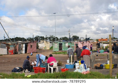 KHAYELITSHA, CAPE TOWN - MAY 22 : A unidentified group of person wash their clothes in Khayelitsha township, the name is Xhosa for New Home on May 22, 2007, Cape Town, South Africa - stock photo