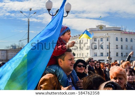 KHERSON, UKRAINE - MARCH 30, 2014: patriotic demonstrators of all ages at the meeting for integrity of democratic Ukraine against Russian intervention with national symbols. - stock photo