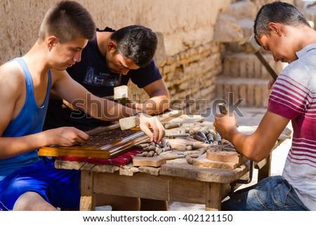 KHIVA, UZBEKISTAN - AUGUST 17, 2015: Craftsman carving patterns on the wooden plate, Khiva, Uzbekistan, Central Asia - stock photo