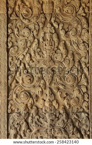 Khmer style sandstoe carvings in the walls of the temple complex of Angkor in Cambodia - stock photo