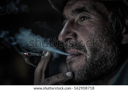 Khorog, Tajikistan - circa September 2011: Man holds cigarette in his hand and smokes in Khorog, Tajikistan. Documentary editorial.
