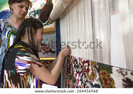 KHUJAND, TAJIKISTAN - MARCH 22, 2015: Women show for public traditional knotting a handmade carpet in central park during Nowruz holiday on 22 of March 2015 in Khujand city, Tajikistan - stock photo