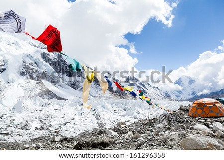 Khumbu glacier in Everest Base Camp, Himalaya Mountains, Nepal. Prayer flags and snow in camping site on rocks. - stock photo