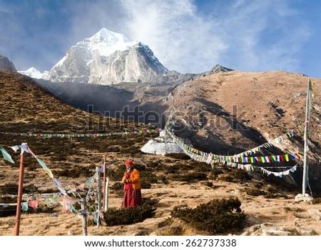 KHUMBU VALLEY, NEPAL - 8th NOVEMBER 2014 - Buddhist monk, stupa and prayer flags near Pangboche monastery and Tabuche peak, life in Khumbu valley on the way to Everest base camp - stock photo